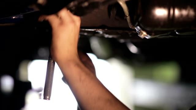 Mechanic tightening the screws under the machine video