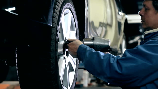 Mechanic unscrews the bolts out of the wheel Mechanic unscrews the bolts out of the wheel of the car tires stock videos & royalty-free footage