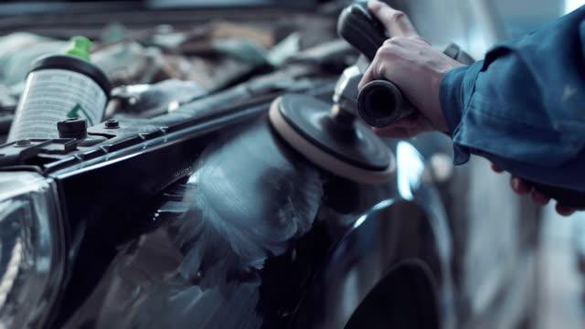 meccanico che utilizza una lucidatrice rotante su un'auto - lucidare video stock e b–roll