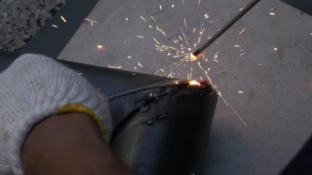 Mechanic welds a piece metal,slow motion video
