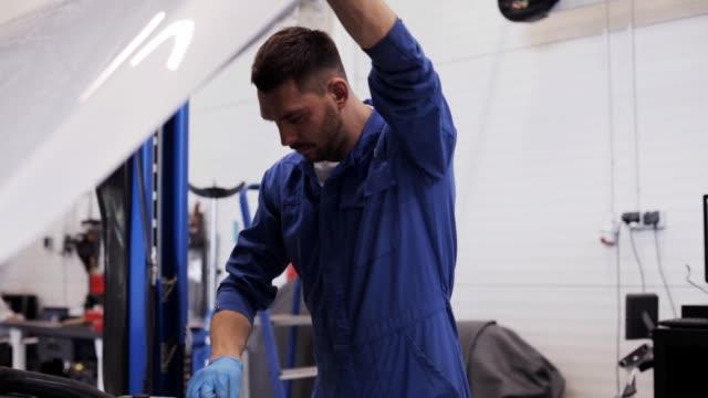 mekaniker med lampa öppna bil huva på bilverkstad - verkstad bildbanksvideor och videomaterial från bakom kulisserna