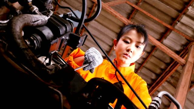 メカニックの女性が車を修理しようとするとします。車のサービス、修理およびメンテナンスの概念を持つ人々。 - 機械工点の映像素材/bロール