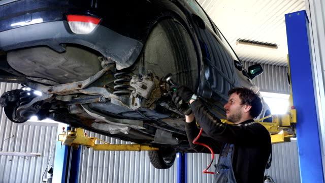mechaniker mann mahlen rostige schrauben mit elektrischem schleifwerkzeug in der nähe von angehobenen auto - litauen stock-videos und b-roll-filmmaterial
