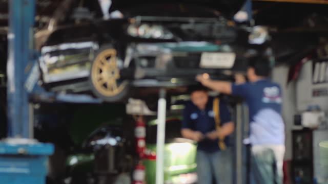 Mechanic working in auto repair garage. Car maintenance. video