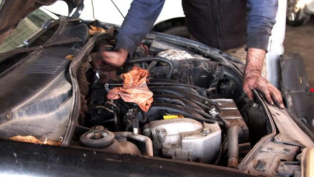 mechaniker arbeitet mit steckschlüssel im automotor - steckschlüssel stock-videos und b-roll-filmmaterial