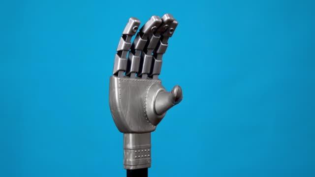en mekanisk hand böjer fingrarna och visar en bergskylt. grå cyborg arm kom till liv och började röra sig på en blå bakgrund. - djurarm bildbanksvideor och videomaterial från bakom kulisserna
