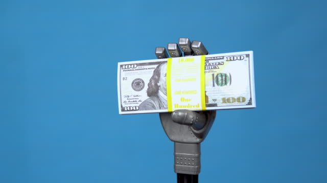 A mechanical hand holds a pack of dollars. A gray cyborg hand holds money on a blue background. 4k