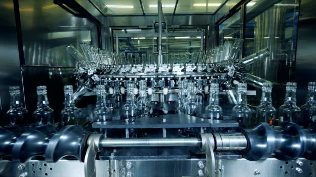 mechanical relocation process of glass bottles - vodka video stock e b–roll
