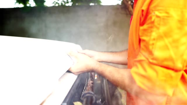 Mechanic's are open bonnet car for maintenance by the smoke rising from the engine video