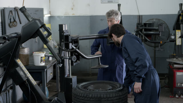 Mechanics at an auto repair shop fixing damaged wheels