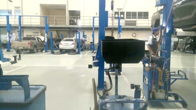 Mechanics repair cars which stand in garage, time lapse video