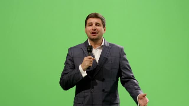 vidéos et rushes de journaliste multimédia avec un microphone parle sur une maquette vert écran en arrière-plan. - interview