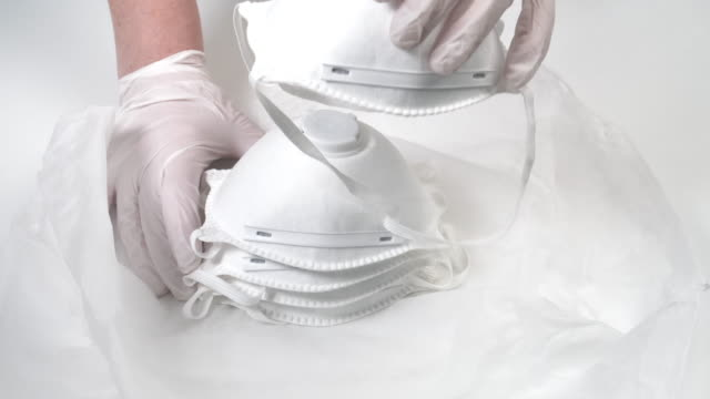 vídeos y material grabado en eventos de stock de asistente médico distribución de máscaras respiratorias - guante quirúrgico