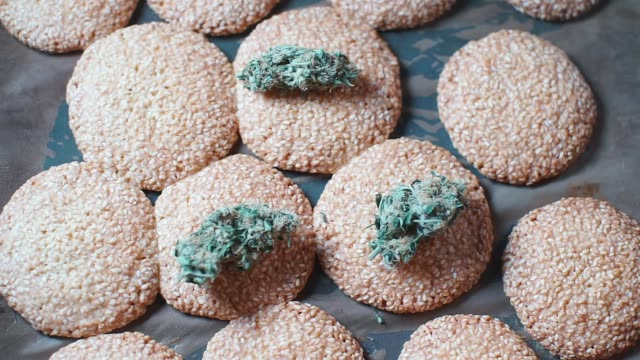 Medical cannabis lies on sesame cookies A close-up of medical cannabis lies on sesame cookies. Food with cannabis oil. hashish stock videos & royalty-free footage