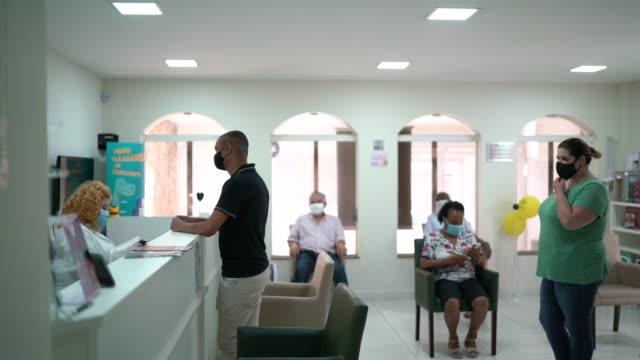 vidéos et rushes de accueil en clinique médicale, patient faisant la queue en respectant la distanciation sociale - vaccin covid