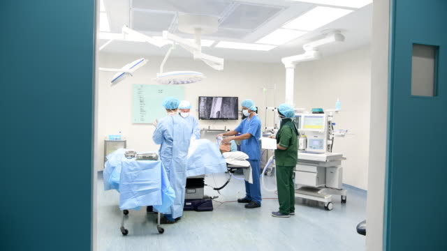 medical consultants operating on patient in hospital room - grandangolo tecnica fotografica video stock e b–roll