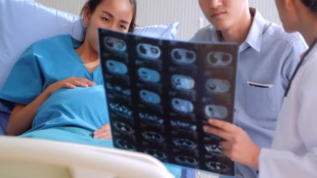 医療相談: 妊娠中の女性と夫がリスニングと x 線フィルムを探しています。医師は、彼女の赤ちゃんは頑丈で健康なことと言います。美しい妊娠中の女の子は、彼女の赤ちゃんを愛してくだ� ビデオ