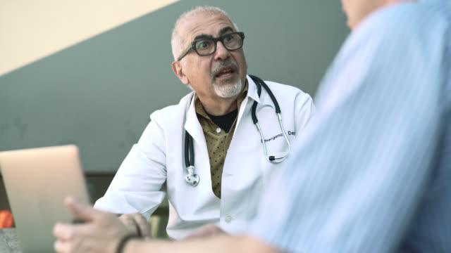 医療相談: 医者、患者、大人の白人男性と話し上級銀の髪の男。 ビデオ