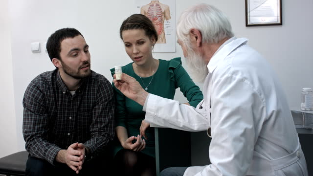 Medical doctor advises pills medication to young couple patients video