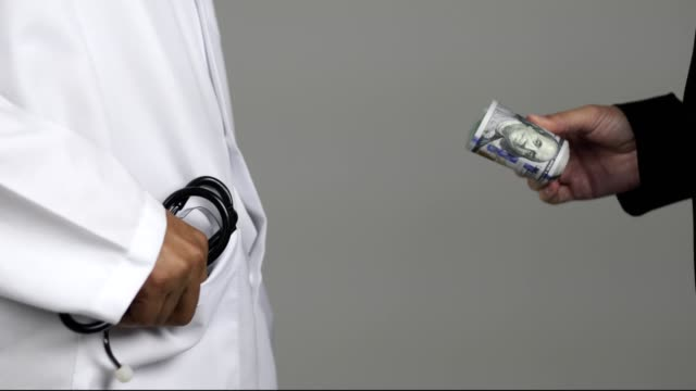 vídeos de stock e filmes b-roll de medical doctor getting money from businesswomen - corruption