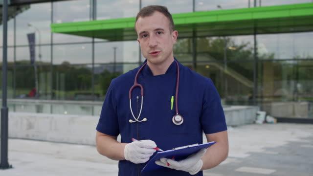 vidéos et rushes de médecin tenant une conférence de presse devant un hôpital - interview