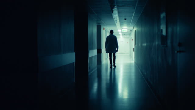 Medical Doctor in the Hospital Walks out of the Dark Corridor and Dramatically Disappears. Sad, Blue Theme of the Loss of Life. Medical Doctor in the Hospital Walks out of the Dark Corridor and Dramatically Disappears. Sad, Blue Theme of the Loss of Life. Shot on RED EPIC-W 8K Helium Cinema Camera. lab coat stock videos & royalty-free footage