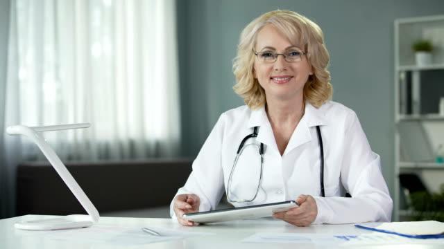медицинский эксперт, рассматривающий результаты тестов пациентов на планшете, сидящем в уютном кабинете - expert стоковые видео и кадры b-roll