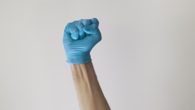 vídeos de stock, filmes e b-roll de mão médica com luva azul fazendo o gesto punho para cima - braço humano