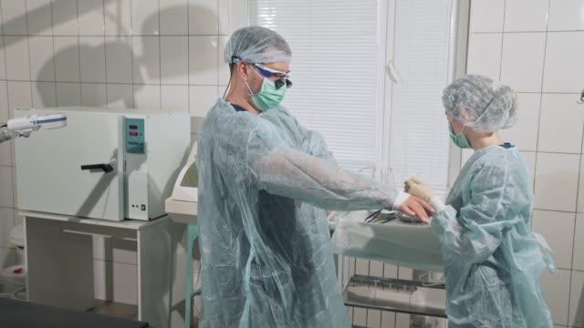 medicinska instrument, begreppet hälsa, sjukhus. en kvinnlig sjuksköterska hjälper en läkare sätta på sterila kläder. professionellt arbete av team av specialister. utrustning på kliniken - aftonklänning bildbanksvideor och videomaterial från bakom kulisserna