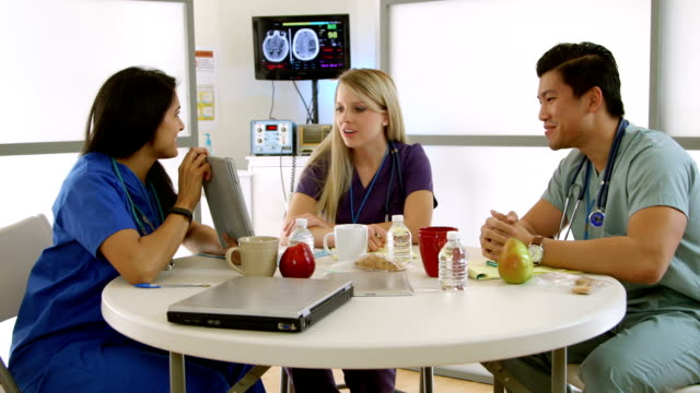 medical interns in hospital break room with tablet Medical interns or nursing students in a hospital break room talk happily about what they see on an electronic tablet pc. cafeteria stock videos & royalty-free footage