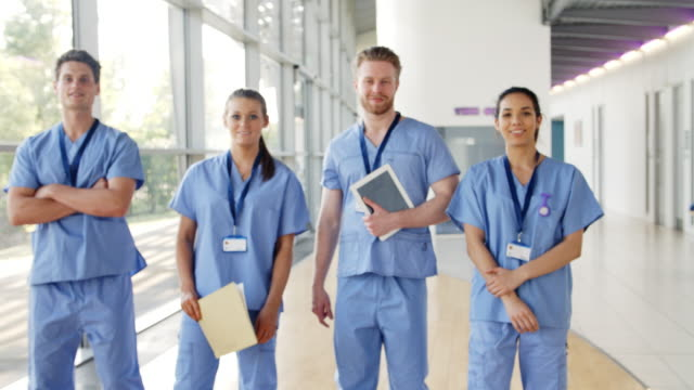 tıbbi stajyerler önlük giyen meşgul hastanede kameraya doğru yürü - cerrahi önlük stok videoları ve detay görüntü çekimi