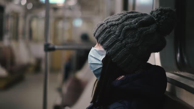maschera medica. una donna con una maschera medica cavalca su un treno della metropolitana. ucraina. kiev. - lombardia video stock e b–roll