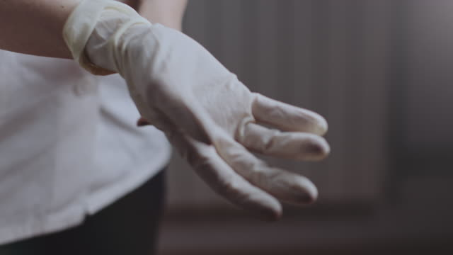 medical nurse puts medical gloves on. stock video - nurse filmów i materiałów b-roll