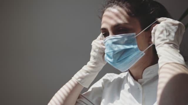 a medical nurse puts on a face a medical mask. 4k stock video - video di protezione video stock e b–roll