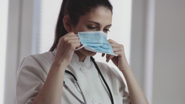 医療看護師は、顔に医療マスクを置きます.4kストックビデオ - 聴診器点の映像素材/bロール