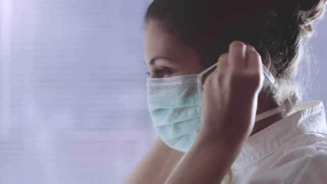 A medical nurse puts on a face a medical mask.  stock video