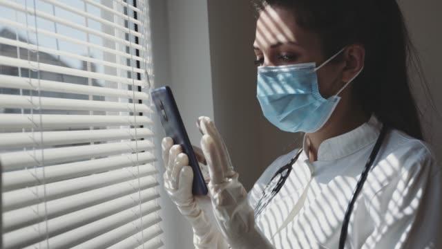 medizinische krankenschwester mit smart phone am fenster - stock video - smartphone mit corona app stock-videos und b-roll-filmmaterial
