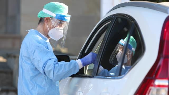 epi를 착용한 의료진은 covid-19에 감염되었는지 확인하기 위해 차 안의 환자에게 pcr을 수행합니다. - covid testing 스톡 비디오 및 b-롤 화면