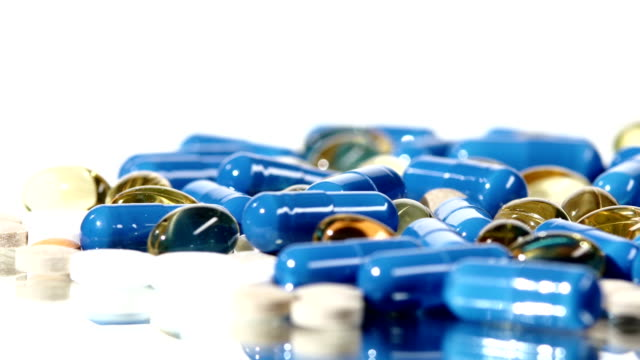 Medical pills, tablets and capsules, rotation, reflection, close up, on white video
