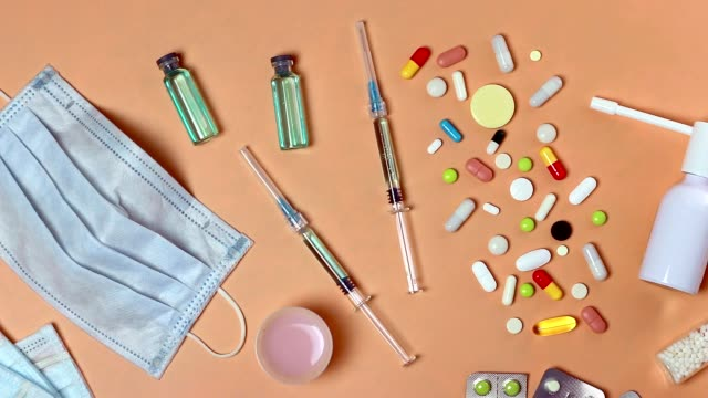 Medical preparation - face masks, medical gloves, ampoules and syringes with vaccine, pills, spray, homoeopathic remedies on peach background. Concept of protection, prevention and treatment of viral diseases