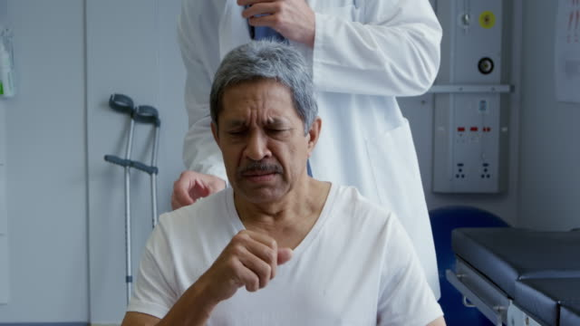 Medical professional and patient at a hospital Front view of a senior mixed race male patient coughing while a Caucasian male doctor wearing a lab coat stands behind him listening to his lungs using a stethoscope coughing stock videos & royalty-free footage