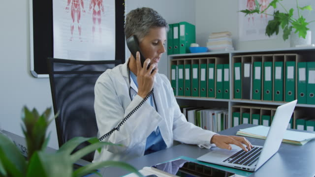 Medical professional at work Side view of a Caucasian female doctor sitting in an office talking on a landline telephone and using a laptop computer landline phone stock videos & royalty-free footage