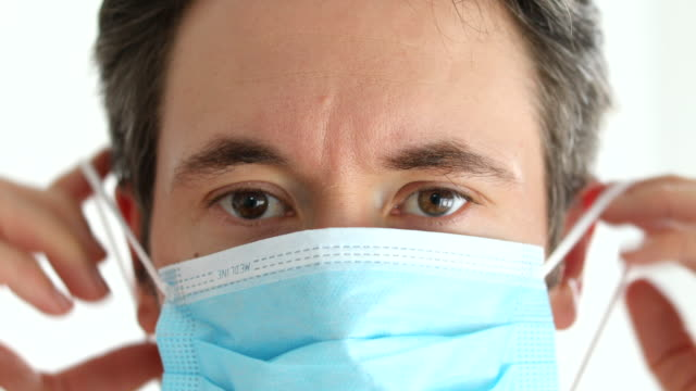 medical professional putting on a safety face mask to prevent from corona virus - face mask stock videos & royalty-free footage
