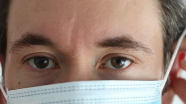 medical professional wearing a surgical face mask - nakładać filmów i materiałów b-roll