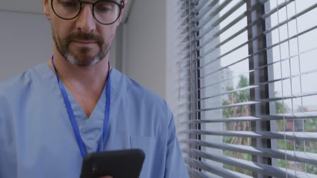 hastanede çalışan tıbbi profesyonel - cerrahi önlük stok videoları ve detay görüntü çekimi