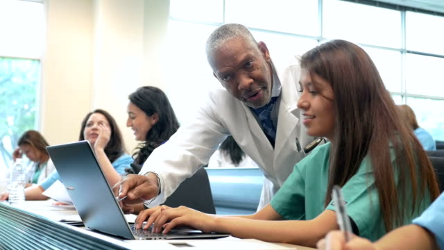 Medical professor teaching diverse nursing students in college lecture hall video