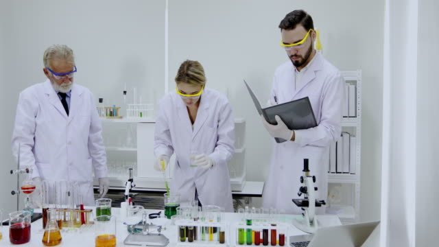 Medical Research and Scientists are working with a microscope and a tablet and Test Tubes, Micropipette and Analysis Results in a laboratory. video
