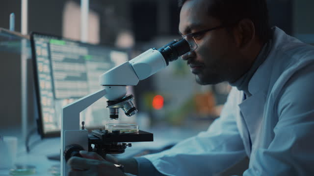 Medical Research Scientist Conducts DNA Experiments Under a Digital Microscope in a Biological Applied Science Laboratory. Multiethnic Lab Engineer in Glasses in White Coat Working on Vaccine. Medical Research Scientist Conducts DNA Experiments Under a Digital Microscope in a Biological Applied Science Laboratory. Multiethnic Lab Engineer in Glasses in White Coat Working on Vaccine. laboratory stock videos & royalty-free footage