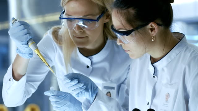 Medical Research Scientist Drops Sample on Slide and Her Colleague Examines it Under Microscope. They Work in a Modern Laboratory. video