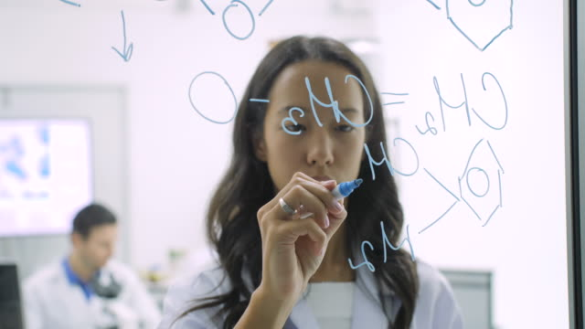 Medical research scientists writes scientific formula on a glass whiteboard with serious face Laboratory, Scientist, Research, Healthcare And Medicine, Equipment chemical formula stock videos & royalty-free footage